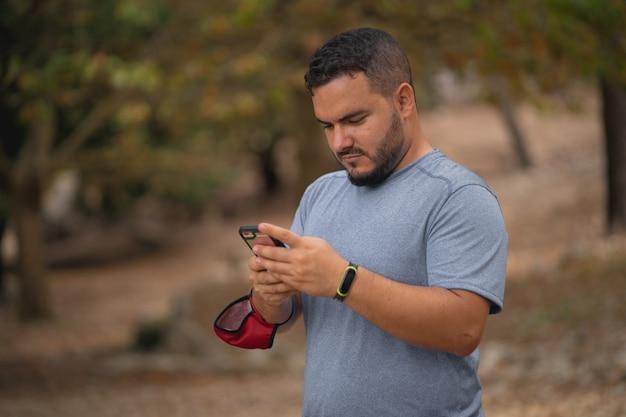 Caminhante usando seu smartphone na natureza, tendo uma máscara no braço