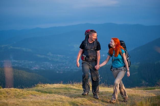 Caminhantes com mochilas andando na área de belas montanhas