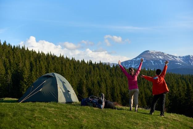 Caminhantes com mochilas no topo de uma colina perto de barracas