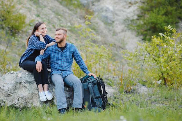 Caminhantes com mochilas relaxando no topo de uma colina e apreciando a vista do pôr do sol