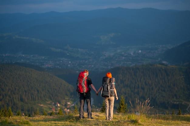 Caminhantes de casal com mochilas de mãos dadas, de pé no topo da colina