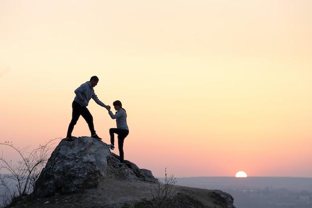 Caminhantes de homem e mulher, ajudando-se a escalar pedra ao pôr do sol nas montanhas. pares que escalam na rocha alta na natureza da noite. turismo, viagens e conceito de estilo de vida saudável.
