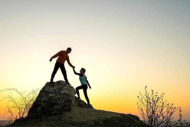 Caminhantes de homem e mulher, ajudando-se a escalar uma pedra grande ao pôr do sol nas montanhas. acople a escalada em uma rocha alta na natureza da noite. turismo, viagens e conceito de estilo de vida saudável.