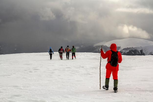 Caminhantes de turistas em montanhas cobertas de neve no inverno e nuvens dramáticas no céu