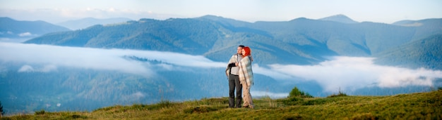Caminhantes do casal cobertos com um cobertor de pé juntos em uma colina