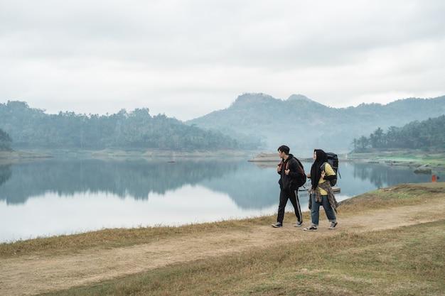 Caminhantes do casal com mochilas andando lado do lago
