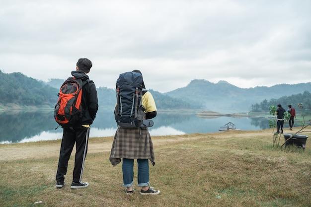 Caminhantes do casal com mochilas, apreciando a vista para o lago