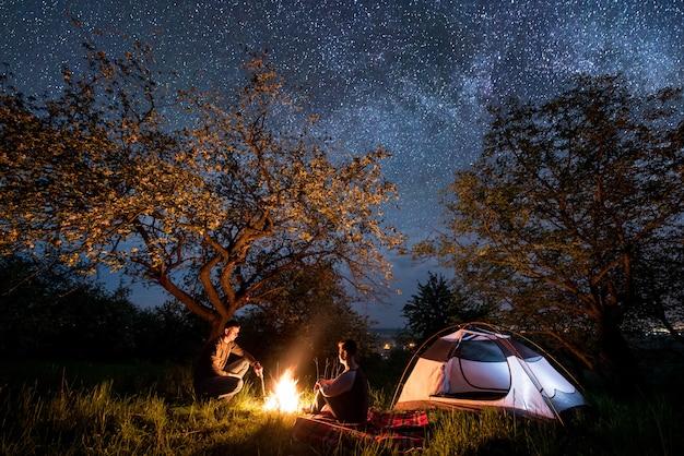 Caminhantes do casal romântico sentado em uma fogueira perto da barraca sob árvores e lindo céu noturno cheio de estrelas e via láctea