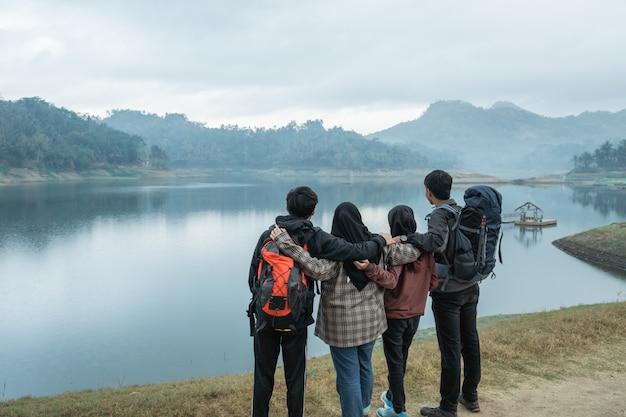 Caminhantes do grupo com abraço, apreciando a vista para o lago