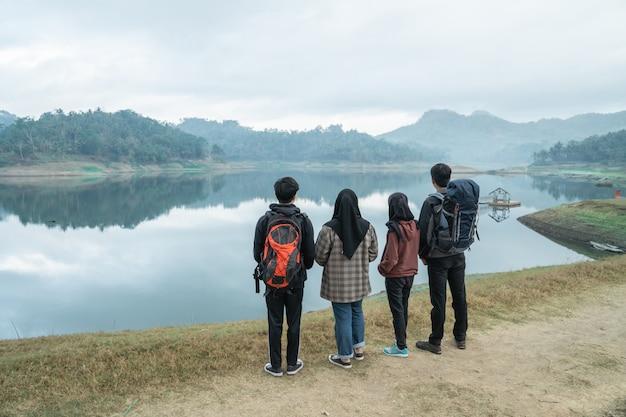 Caminhantes do grupo com mochilas, apreciando a vista para o lago
