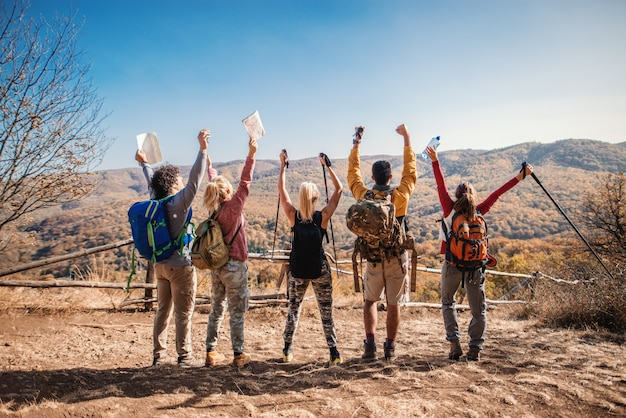 Caminhantes felizes em pé na clareira com as mãos no ar e olhando a bela vista