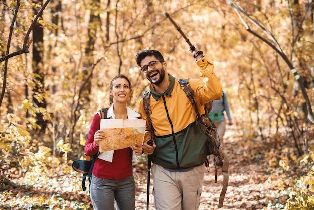 Caminhantes felizes que exploram a floresta no outono. mulher segurando o mapa enquanto homem apontando com pau no caminho certo.