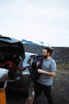 Caminhantes pegando coisas do porta-malas do carro