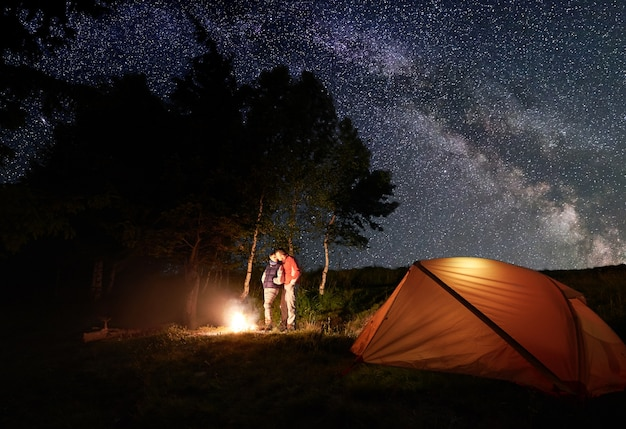 Caminhantes perto da fogueira e barraca no acampamento noturno