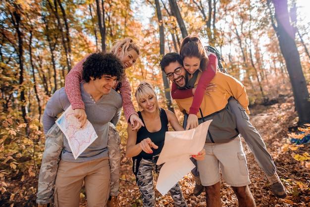 Caminhantes segurando suas namoradas nas costas enquanto olha para o mapa.