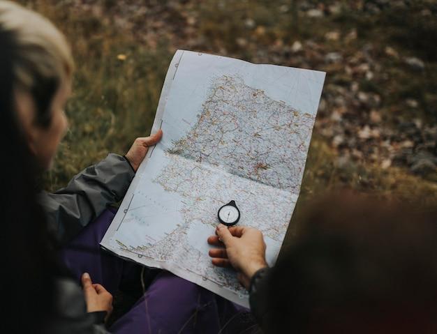 Caminhantes usando uma bússola e um mapa