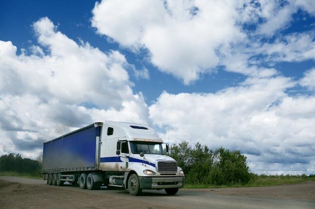 Caminhão andando na estrada sob céu nublado