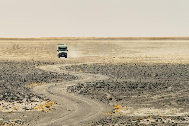 Caminhão andando por uma estrada rochosa curvilínea fazendo poeira