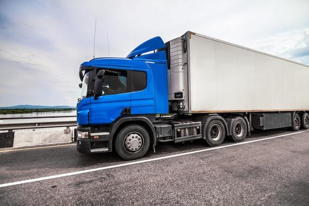 Caminhão azul em uma estrada com reboque refrigerador