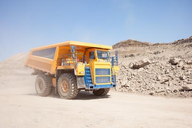 Caminhão basculante amarelo movendo-se em uma mina de carvão