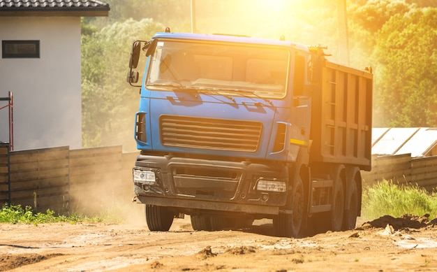 Caminhão basculante azul ao pôr do sol no canteiro de obras está se movendo em meio a poeira e sujeira, foto de máquina pesada