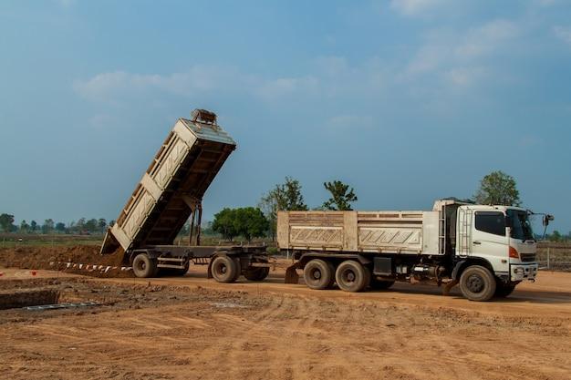 Caminhão basculante de reboque descarregando solo ou areia no canteiro de obras