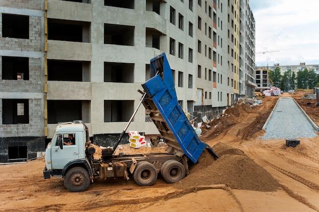 Caminhão basculante descarrega solo e areia no canteiro de obras