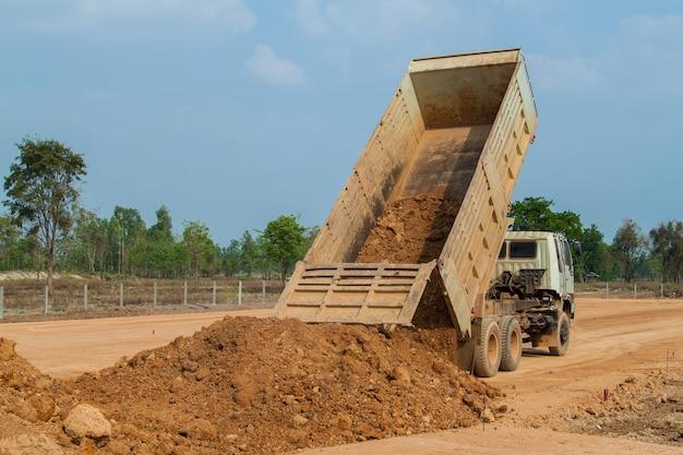 Caminhão basculante descarregando solo ou areia no canteiro de obras