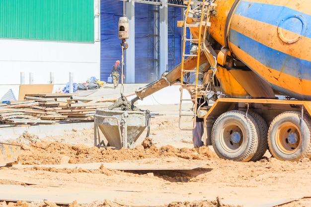 Caminhão betoneira despejando concreto líquido no balde do guindaste de torre