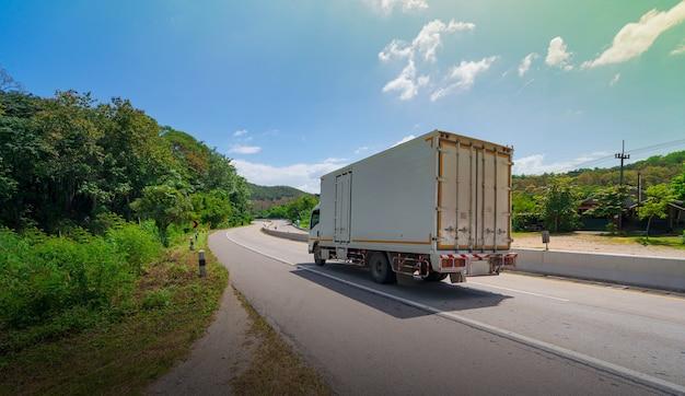 Caminhão branco dirigindo na estrada de asfalto em paisagem rural pela manhã