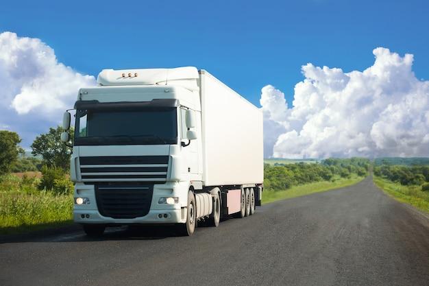 Caminhão branco se movendo em uma estrada no verão