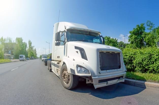 Caminhão branco sem reboque e carga na estrada.