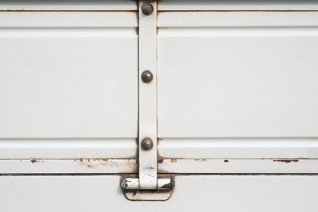 Caminhão branco velho com oxidado, fundo e superfície brancos da pintura do metal do grunge.