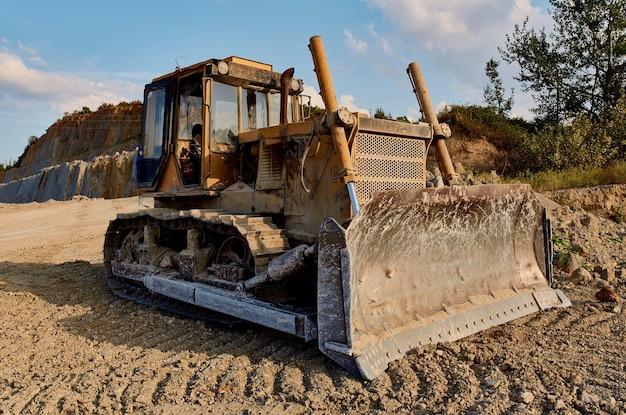 Caminhão cavando terreno para escavadeira de construção, cascalho, areia, árvores, céu azul