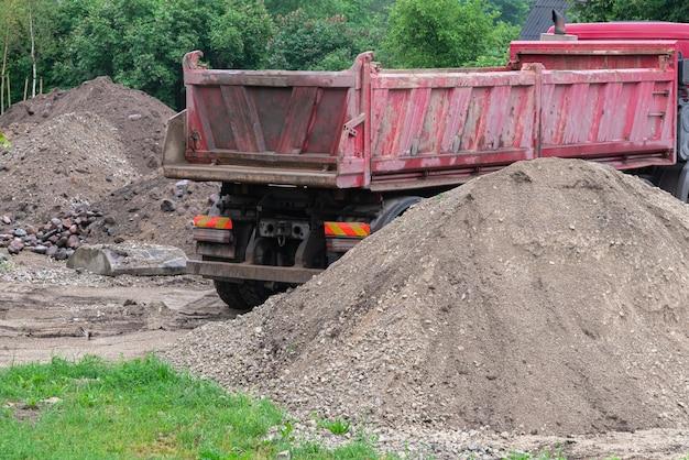 Caminhão da escavadeira entre a areia no canteiro de obras.