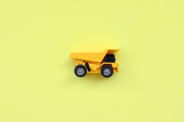 Caminhão de brinquedo amarelo pequeno na textura de papel de cor amarela pastel moda no conceito mínimo
