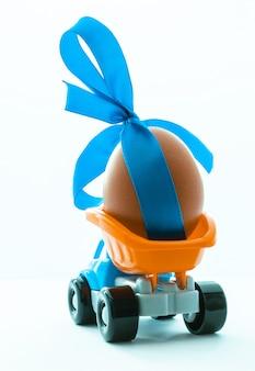 Caminhão de brinquedo colorido com um ovo de galinha nas costas em um fundo branco