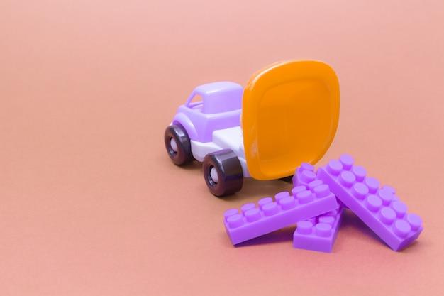 Caminhão de brinquedo descarrega os detalhes dos blocos em um fundo rosa