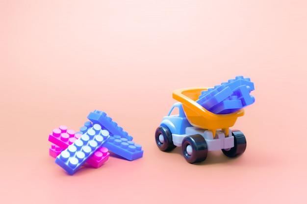 Caminhão de brinquedo modelo de carro com blocos de construtor no fundo rosa