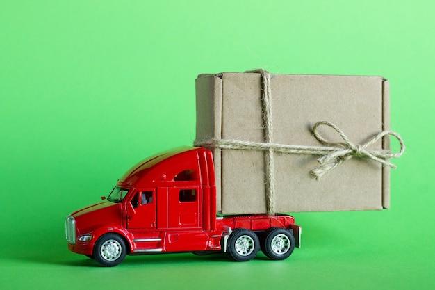 Caminhão de brinquedo vermelho entrega um pacote em uma caixa de papelão artesanal em um fundo verde pastel. entrega de mercadorias, presentes ou conceito de doação.
