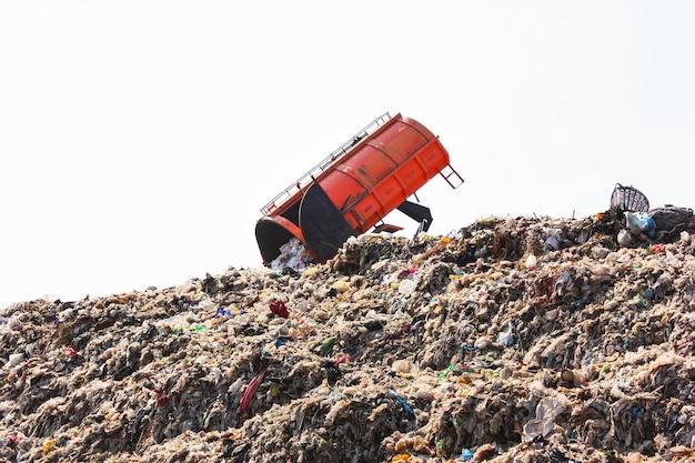 Caminhão de garras despejando o lixo em grande lixão municipal em aterro sanitário.