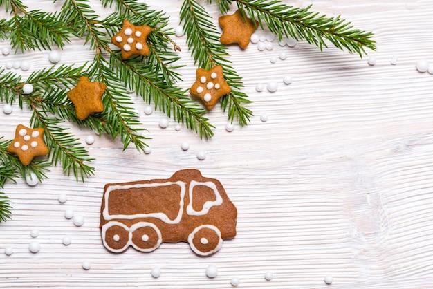 Caminhão de gengibre e estrelas na mesa de madeira com ramo de abeto