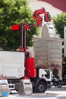 Caminhão de lixo coletando lata de lixo