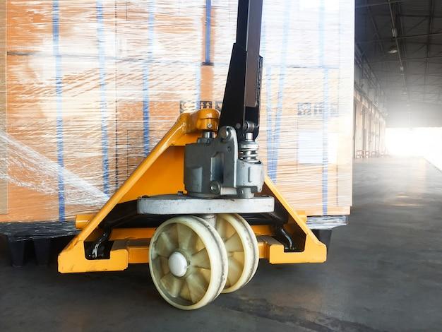 Caminhão de pálete da mão com a pálete da expedição para exportar.