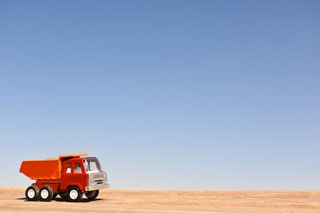 Caminhão de reboque de brinquedo colecionável em escala piso de madeira e fundo de céu azul macro