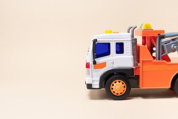 Caminhão de reboque laranja de brinquedo no banner de fundo bege com espaço para texto.