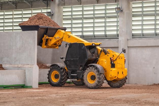 Caminhão do carregador da roda que trabalha no picador de madeira da fábrica