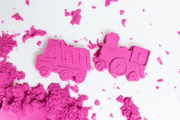 Caminhão e trem feitos com uma areia cinética cor-de-rosa em um fundo branco.