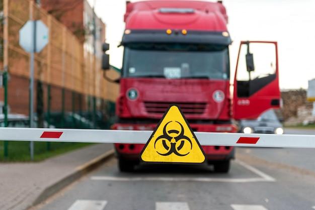 Caminhão em pé na barreira com um sinal de aviso de vírus