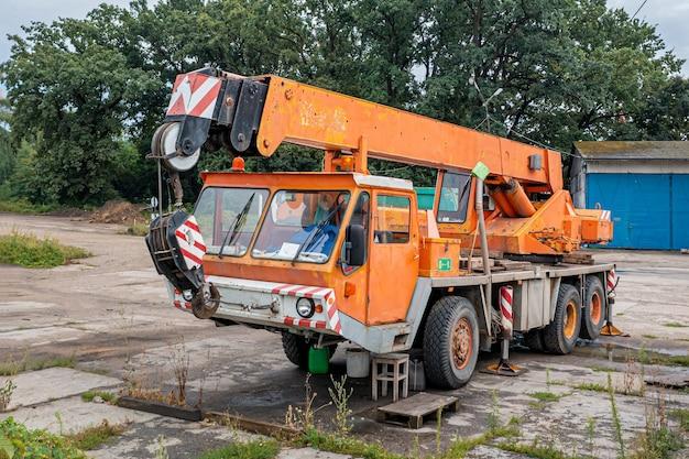 Caminhão guindaste laranja velho parado no estacionamento